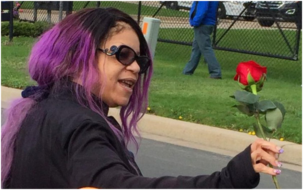 Tyka Nelson, holding a rose with her hairs colored in purple, to honor the memory of his lost brother