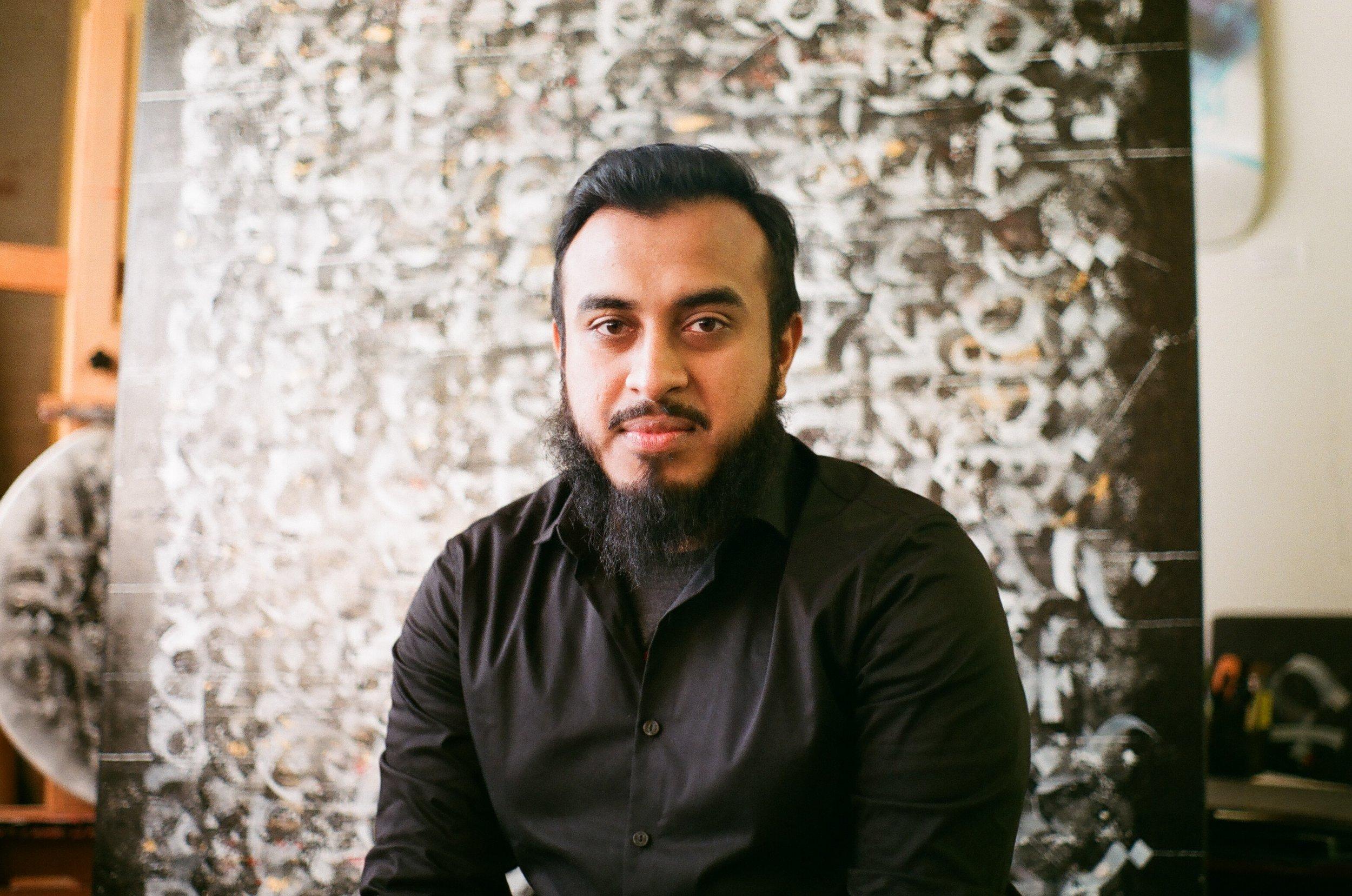 Zaman sitting with his art in his studio in Buffalo, NY