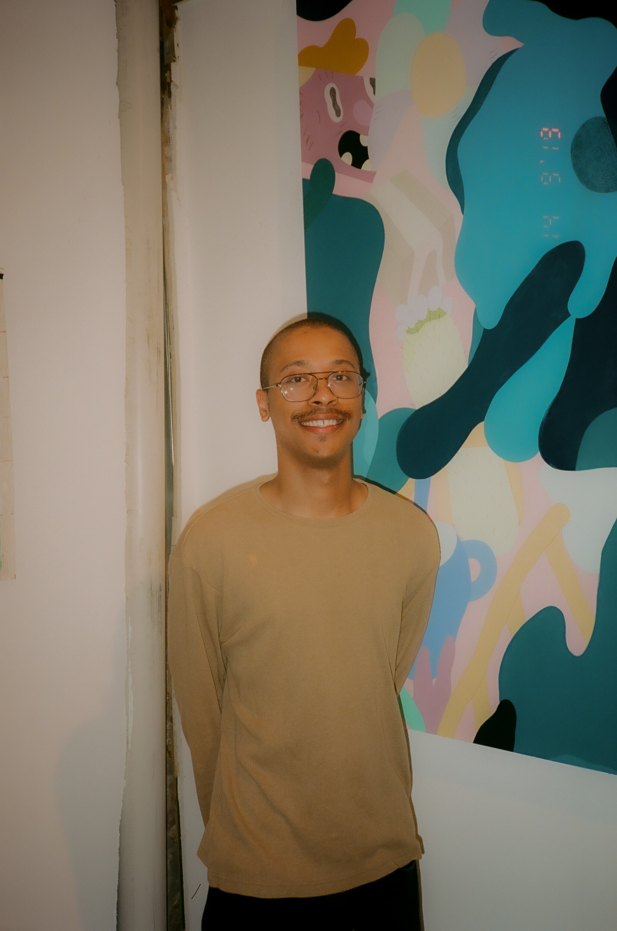 SALUT standing with his work during a pop-up exhibit with UUU Art Collective in NYC in September, 2019