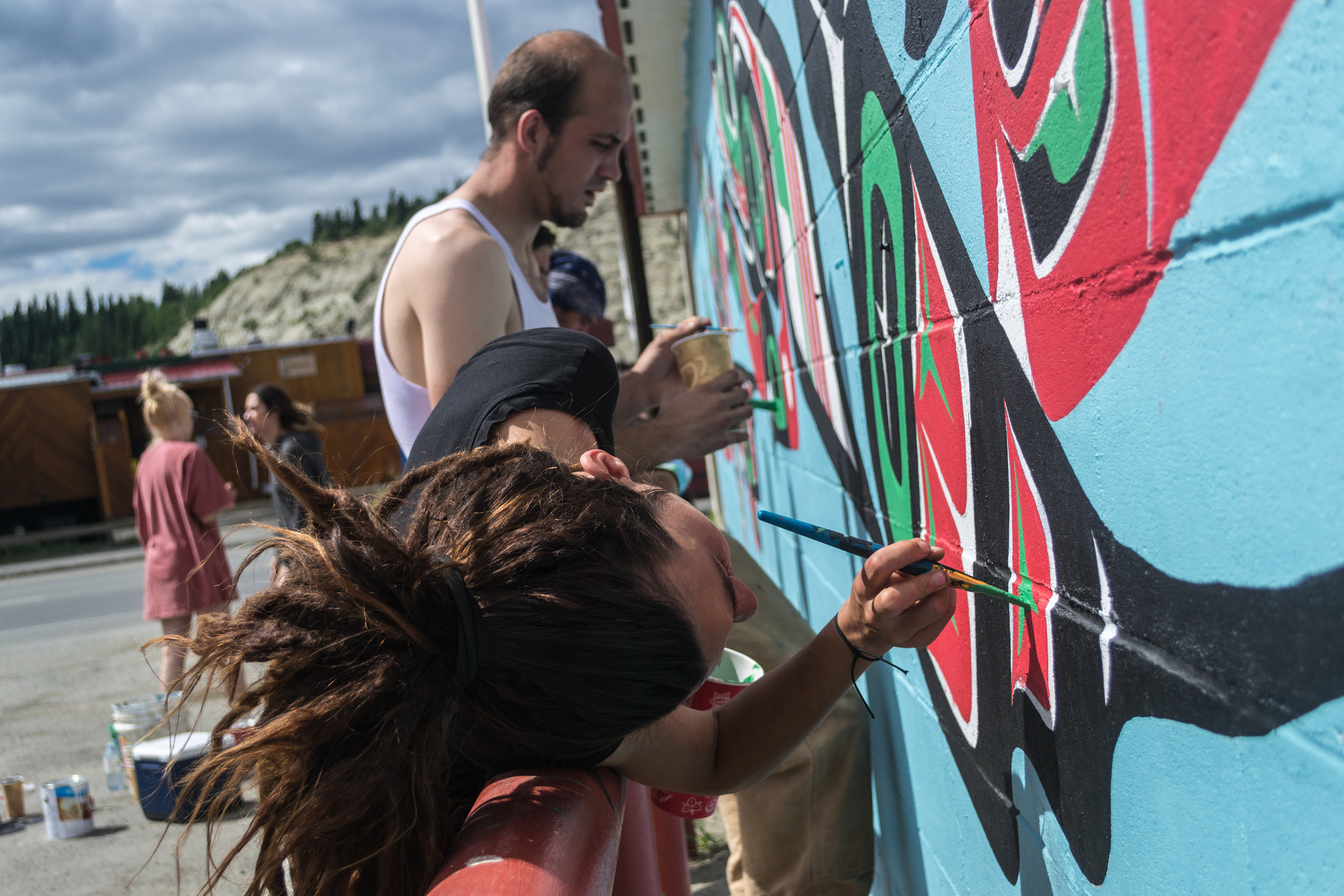 Indigenous and non-Indigenous artists work together to design and paint the murals on walls across Whitehorse.
