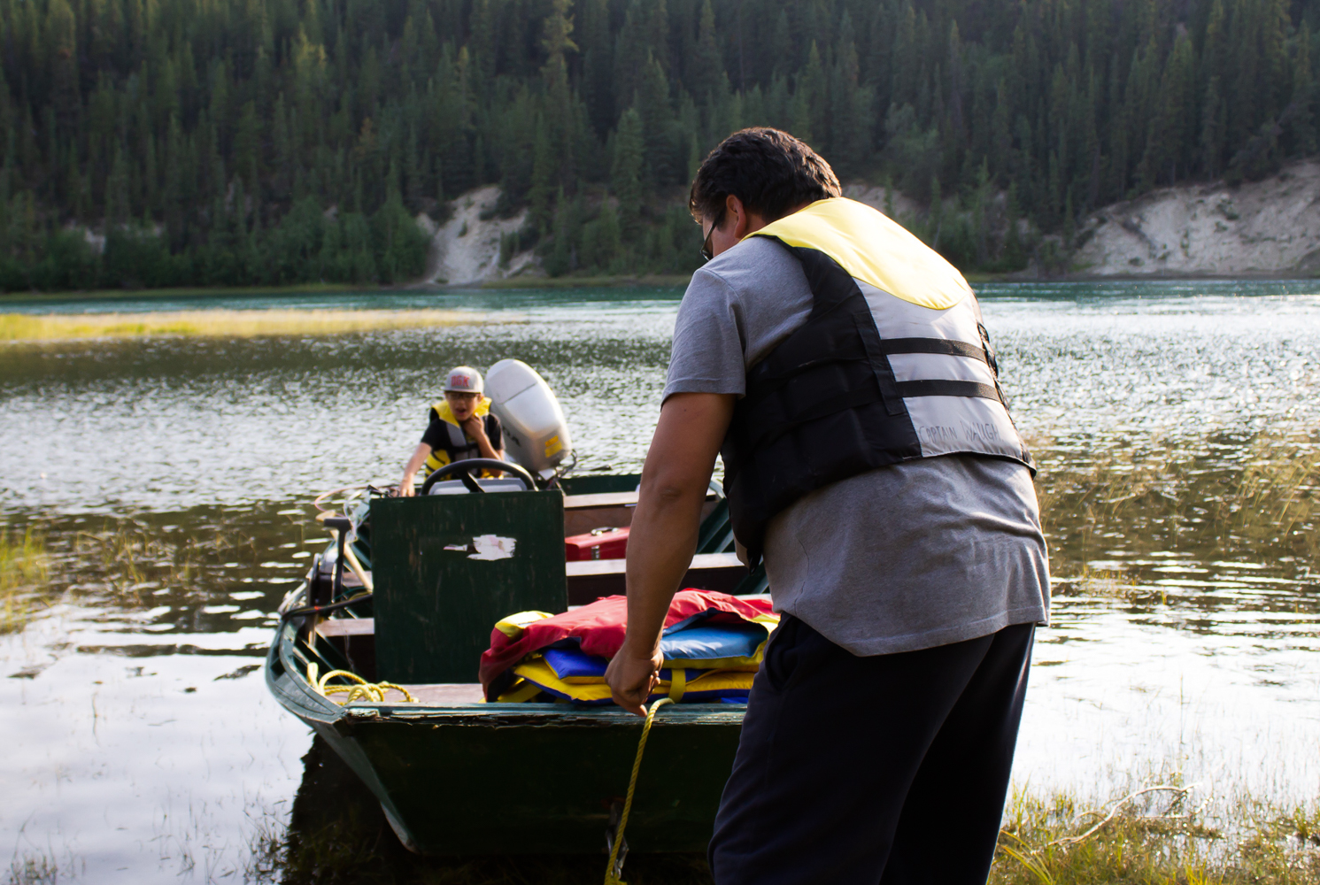 Charles Waugh pushes his family's boat off the dock. They are going out onto the Yukon River to check their net for salmon. Photo by Kiera Kowalski