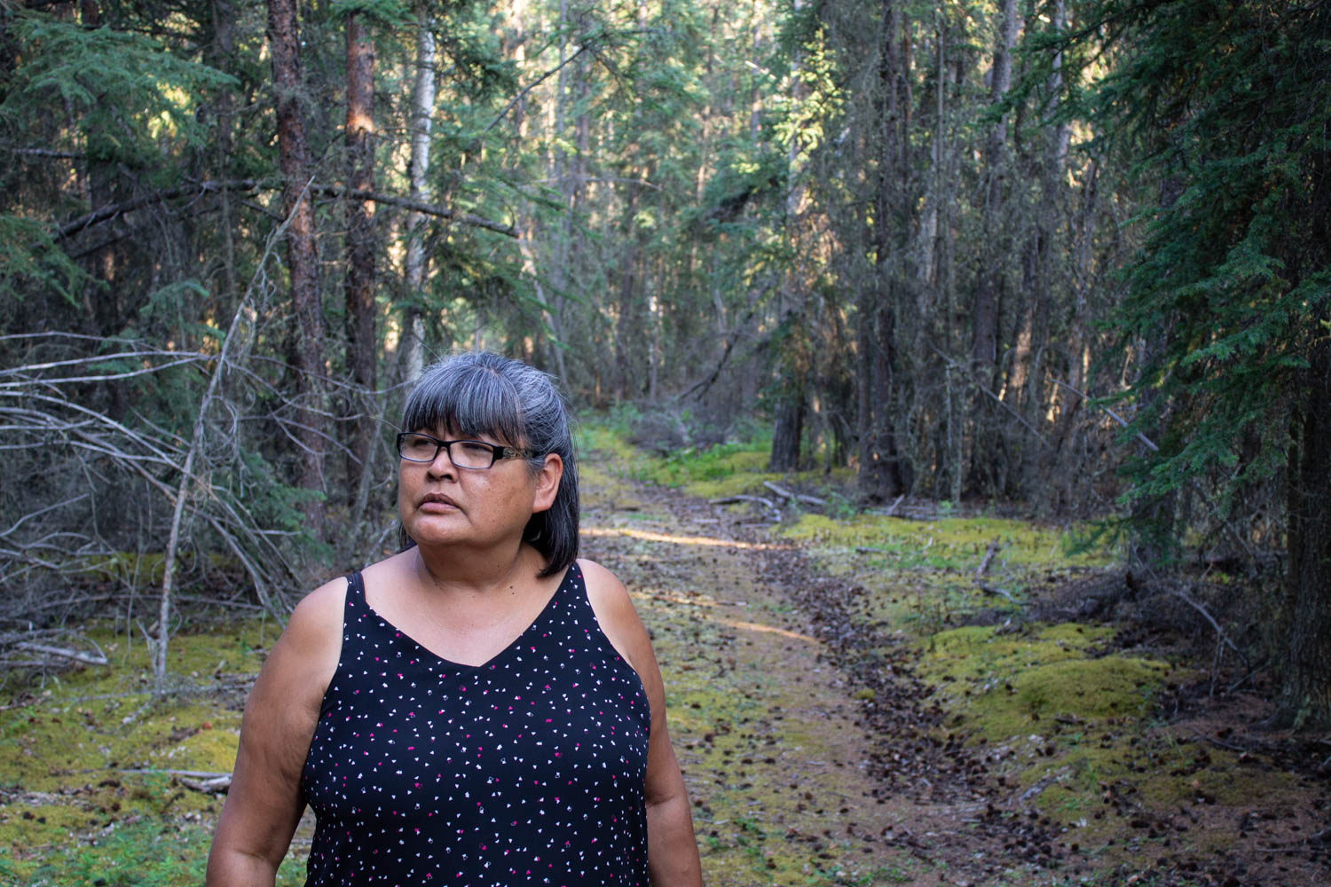 Dorothy Sam stands in a small clearing in the wooded area surrounding her fish camp. The path that she stands on links the different locations throughout the camp — from her kitchen, to the salmon drying racks to the dock where her family's boat sits. Photo by Kiera Kowalski