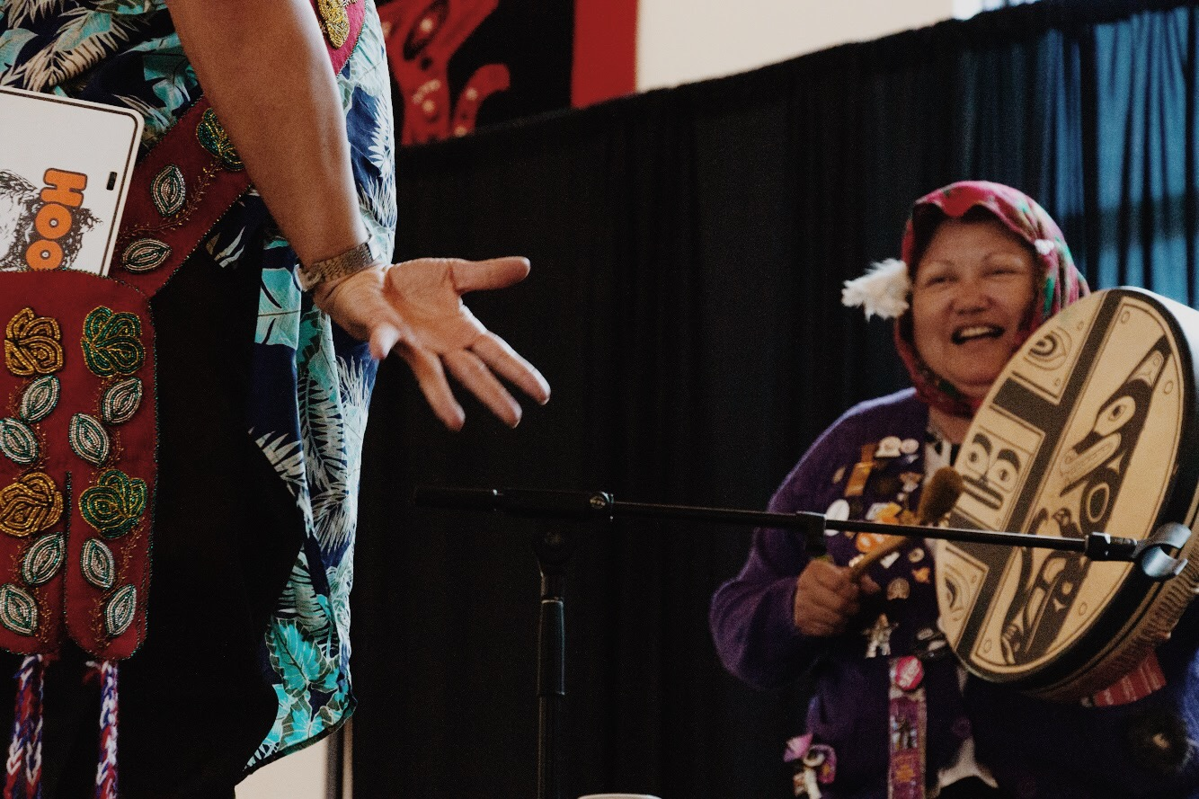 Shorty drums while Ghastant' Aucoin performs the grouse dance, a traditional Tlingit mating dance.
