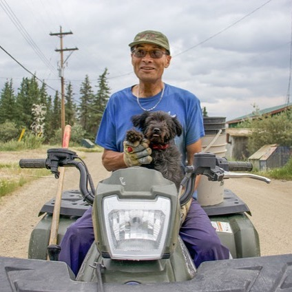 """When you ask Allan Benjamin how old he is, he'll say: . """"60 plus two years."""" . When you ask him how long he's lived in Old Crow, he'll say: . """"60 plus two years."""" . For Allan, Old Crow is home through and through. He says he and his dog, Puddles, love everything about living here. . """"Picking berries, cutting wood, hunting, running, snowshoeing, taking Puddles for a ride, feeding the mosquitoes,"""" he says, listing some of his favourite things to do. . Allan also likes to spend time drawing. He draws cartoons for What's Up, Yukon? using two original characters called Didee and Didoo, which means grandfather and grandmother in Gwich'in. . Allan says he enjoys drawing his cartoons because it brings other people joy. . """"I like to make people laugh."""" . . (story by @meaghanbrackenbury ) #weareoldcrow #storiesnorth #oldcrowyukon #exploreyukon"""