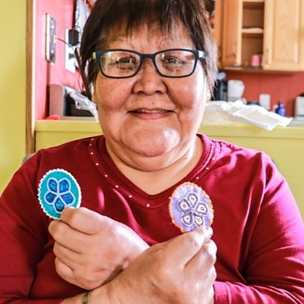 """Elizabeth Kyikavichik works at Old Crow's daycare five days of the week, but her real passion is beading. . Elizabeth says she got into beading by seeing the work of others. . """"I think how I got familiar with beading is just by seeing other people wear garments that are beaded, like boots, slippers, mitts,"""" she says. . """"As a child, I liked what I saw, and later on when I entered into the school program, the older girls at the residential school were doing beading that they brought from home. They beaded, and they did such a beautiful job, and I was able to get hold of some beads, and just by watching them I caught on how to bead."""" . Recently, she has learned how to make beaded magnets like the ones she is holding in the picture. She is also currently beading a pair of slippers for herself. . According to Elizabeth, the hardest part about beading is consistency. . """"At the beginning it's not what you expect or your beading does not compare with the ones you've seen out there,"""" she says. . """"The more you practise, the better you get at it, so that's how I worked my beading. At the very beginning of beading I didn't like my work. But with anything you do, there's always a beginning and there's always results."""" . Elizabeth says what makes someone better at beading is their passion for the craft. . """"If you want to do a good job, you got to have lots of time and patience and passion. Otherwise, what's the point? You don't want to do something you don't like — that's not developing passion for beading."""" . . (story by @meraljamall ) #oldcrowyukon #exploreyukon #weareoldcrow #storiesnorth"""