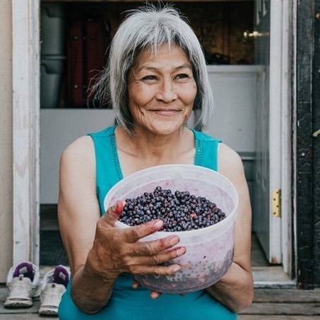 """Plump and sweet. . It's blueberry season north of the Arctic Circle. . Christine Nukon called us over to her front porch to ask what we were doing in Old Crow. . """"Learning about life here,"""" we said, in unison. . Christine smiled and told us we'd want to get out to pick berries while we're in the community. . She had just found a patch near the airport and had purple fingers and lips to prove it. . She says the berries ripened a bit early this year. And, they're really good, she added, offering us a handful. . This post is part of a Stories North series called: We Are Old Crow.Check back to meet more people who call this place home, some folks who've travelled here and their perspectives about life and how it's changing. . . (Photo and post by @kaninaholmes ) #oldcrowyukon #travelyukon #weareoldcrow #storiesnorth"""