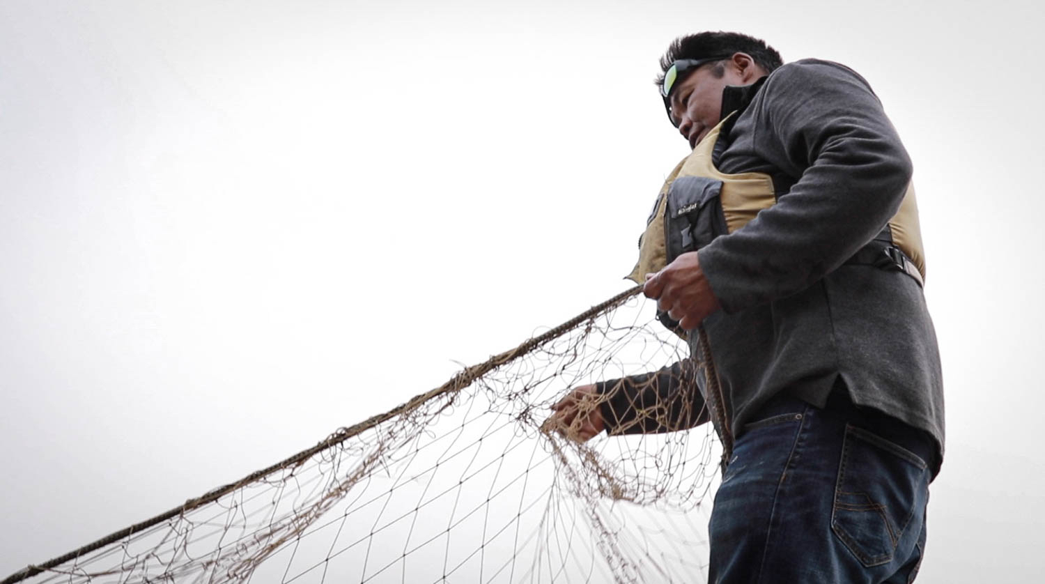Robert Kyikavichik checks the fish nets for salmon along the Porcupine River. (Photo: Meral Jamal)
