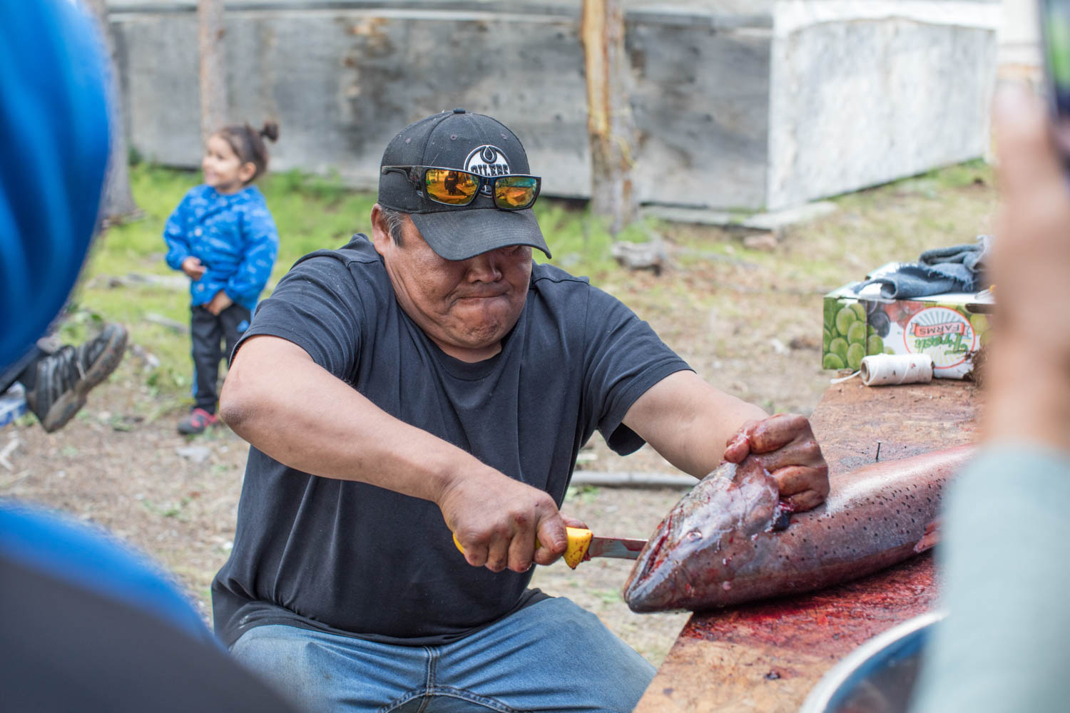 Robert Kyikavichik shows Old Crow youth how to fillet a freshly caught Chinook salmon. (Photo: Kanina Holmes)