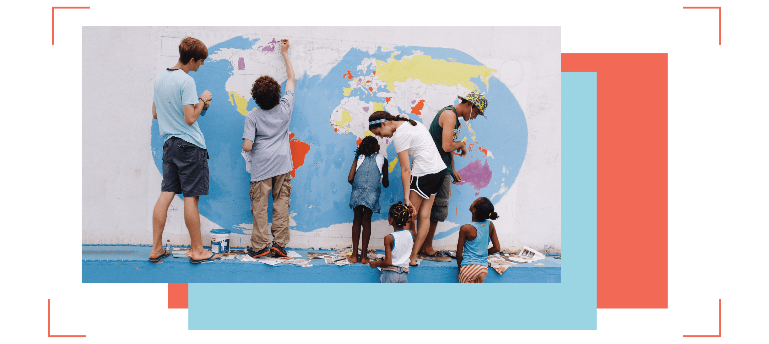 Students and young children paint a wall mural depicting a map of the world.