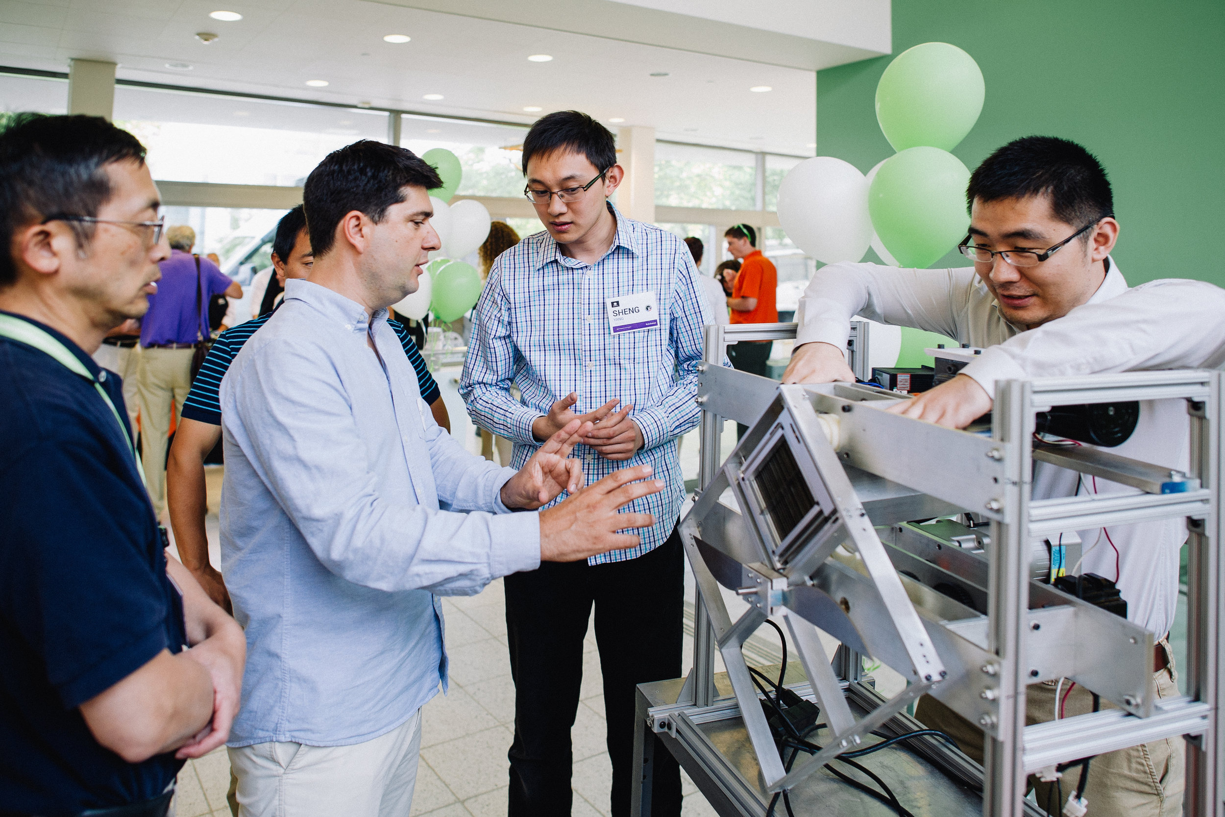 Students and professors reviewing an electrical engineering gadget in an academic building.