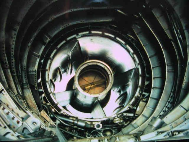 "This is a photo of the center body and inlet of an A-12 looking forward from inside the nacelle with the engine removed.The center body is where the spike is mounted. The raised bumps on the perimeter are called mice and the openings in between them are the by pass door vents.The AFCS and later the DAFICS computer controlled the spike and by-pass doors to bleed off air and control air flow at the engine. (GO FAST MACHINE)  Axisymmetric Supersonic Variable Geometry Inlets The conical tip in front of the engines are called the ""spike"". The spike moves forward and aft within the nacelle opening. Some people think, that as the spike moves aft the opening gets larger. This is not exactly true.  A simplistic explanation- What happens is, the very front of the opening gets bigger but the area inside actually gets smaller. The position of the spike controls the position of the super sonic shock wave of air pressure entering the nacelle. The forward by-pass doors help stabilize and maintain the air pressure entering the front of the engine. All the extra air unneeded air is diverted around the compressor section and directly into the afterburner ejector nozzle. What this does is give higher volumes of air at altitudes where little air exist.  The reason why the SR gets better fuel mileage the faster it goes, is because at those altitudes the air is so thin that there is less drag on the aircraft and the inlets create air pressures at better than sea level.  The technical and engineering aspects of these inlet are vast and most people can't understand exactly how they work. I myself have spent many many hours with my body wedged up inside SR-71 inlets measuring, mapping dimensions, removing, rebuilding, and installing inlet assemblies. I can tell you this, unless I had a need to know, I didn't ask.  Did Skunk Works develop the ""Perpetual Motion Machine""? Even thought by this theory one might think this is the ultimate perpetual motion machine, it is not. The SR's speed is limited not by power but by temperature. As speed increases so does the temperature and when these alloys heat up bad things start to happen. They start to expand, warp, and buckle. their characteristics start to change and weaken. The SR crews were not to let inlet temperatures exceed 427 degrees C."