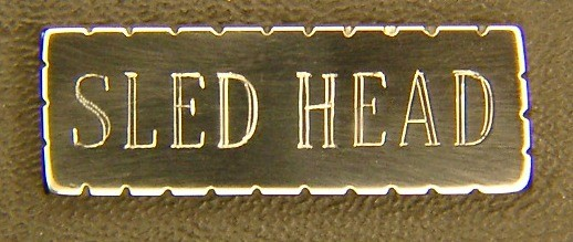 "Thanks for this dedicated website! I've read about your making of custom jewelry from SR-71 parts, and I'd like to know if you could make a pin that spells out ""SLED HEAD"" for me. Please let me know if this is do-able, and, if you would be so kind, I'd like to get a rough idea of how much a one-off item like this will set me back.  I was a Sled Head long before I knew the term existed. I've been quite interested in that amazing bird since I first heard about her in 1968 or so. I must've been in junior high when the seemingly 'double-booms' happened, and we all got a huge kick out of the noise---made the windows rattle in that old school building. We theorized it was 2 jets breaking the proverbial sound barrier close together (what did we know).  A cousin who was a 2-star hinted around as to the source of that unusual 'double.' Eventually, I acquired photos and a bit of info. Been fascinated with that aircraft ever since.  In the mid 1990s, I was in Iowa for an internship in compounding pharmacy, and I wanted to go to the SAC base near Omaha to see the SR-71 that was supposed to be there in their museum. Turns out the museum was locked up pending the arrival of funds to build the new SAC museum near Aurora, Nebraska.  Nevertheless I persisted, and eventually I was allowed in to where the SR-71 was stored. Eeee gads! It was as though they had her in someone's back yard: she was out in the weather, resting just on her own tires in the hard-packed dirt, with WEEDS growing up around her! Tragic.  Still, it was a heart-stopping thrill to see a Blackbird up close & personal. And, now that I'm a docent at the Seattle Museum of Flight, I get to talk about the Blackbird 'family of aircraft' to other soon-to-be- Sled Heads every week ---yeeee haw!!  Once a year (between Christmas and New Years' Day) we have 'Blackbird Tip-to-Tail Tours' wherein, twice daily, my fellow docents and I competitively take turns giving one-hour (ok, they usually go on for at least TWO hours; but they're officially one hour) tours of this miraculous superemminent aircraft.  How delightful it is to be required to study up on her, and to be quizzed unmercifully about her! So, naturally, I attend (with great enthusiasm) Brian Shul's annual presentations at the Museum of Flight---it's a joy and a pleasure each and every time I have the privilege of hearing him speak! And I have the pleasure of owning, reading, and enjoying his eye-popping informative books about this stunner of an aircraft. Criminey, I'm running out of superlatives, so will sign off for now.  Dan, those are gorgeous! You talented genius you! BOTH pins are truly beautiful!! And I'll take 'em both please. Thanks once again for these amazing pins. And thanks, especially, for your (continuing) service to our Country! All the Best to Dan, Katie Wasem, SLED HEAD"