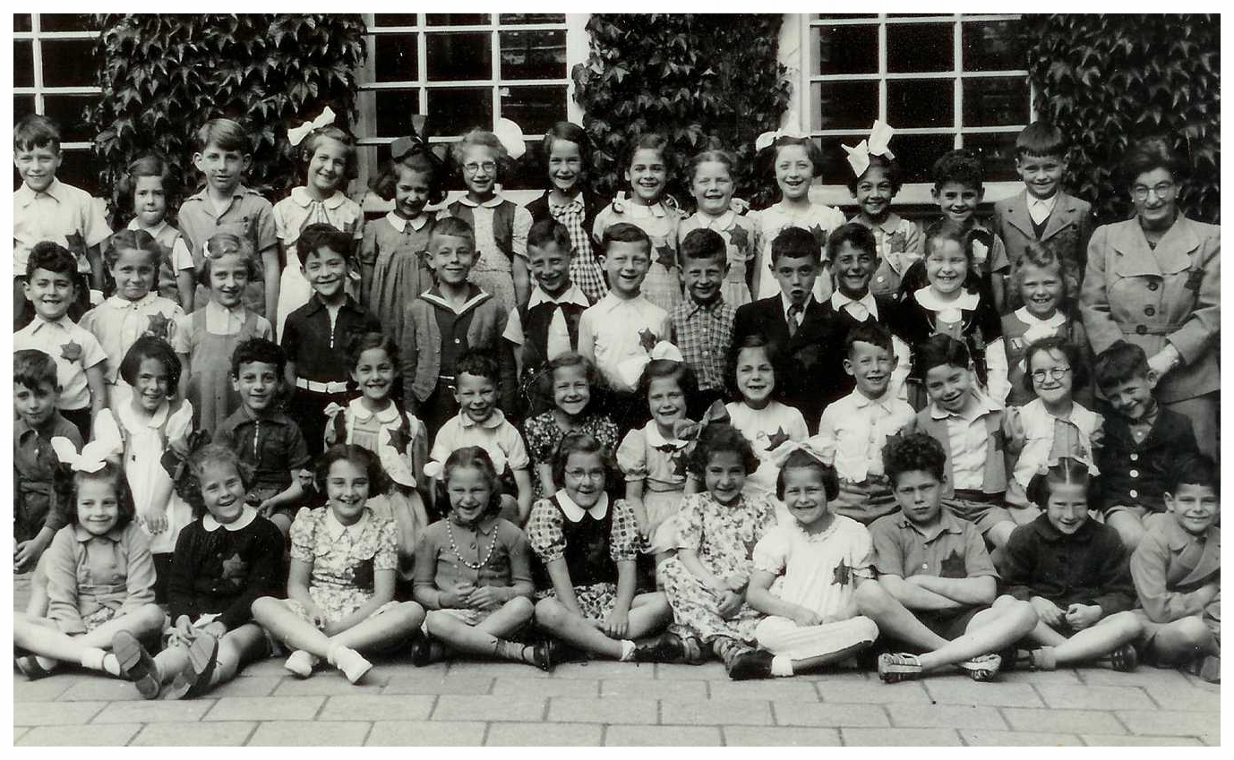 Tutti's class photo - 1942. Jewish school children wearing the mandated Jewish star. Tutti is standing in the third row, 2 places left of the teacher.