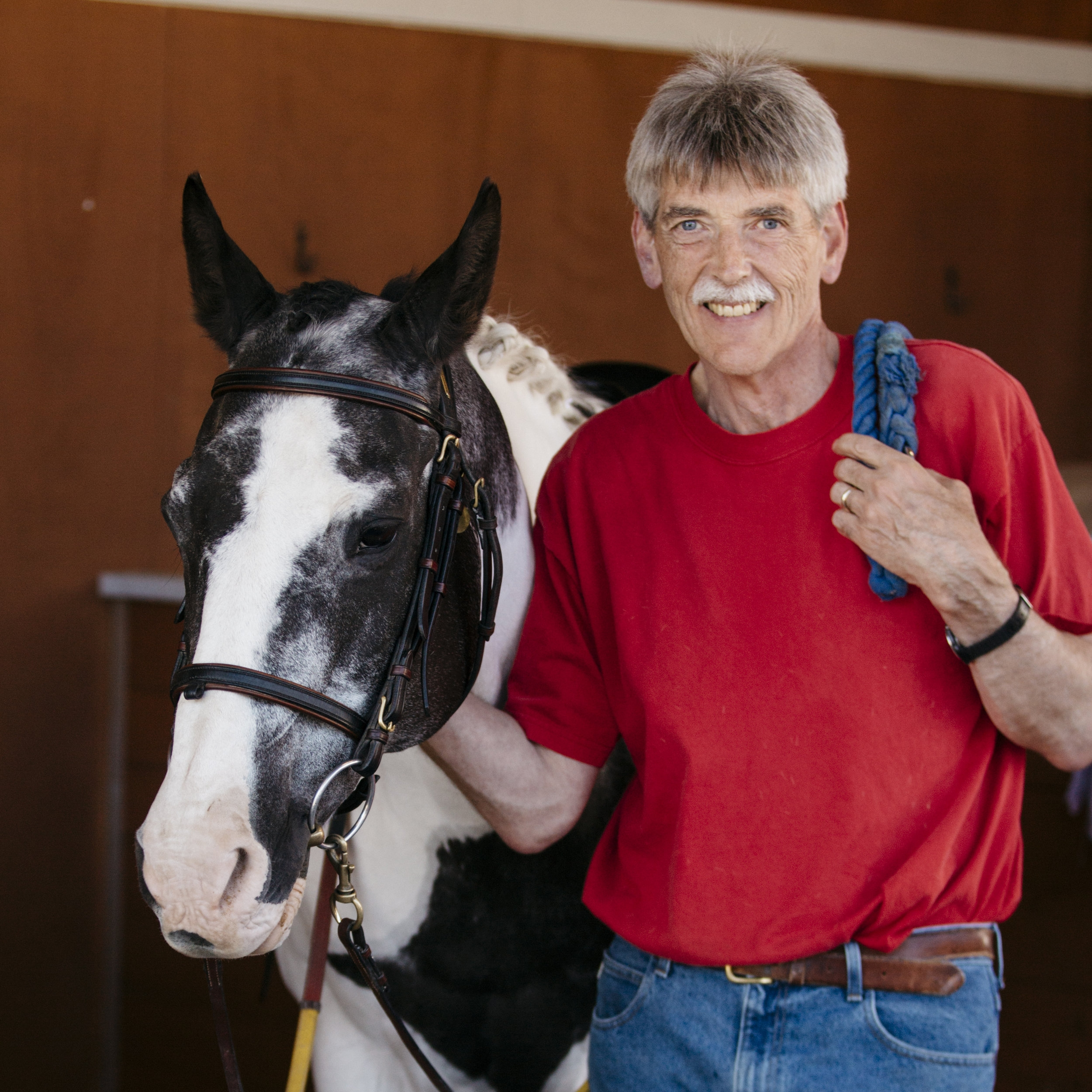 Man in a red shirt and jeans petting a white horse with black markings and ears.