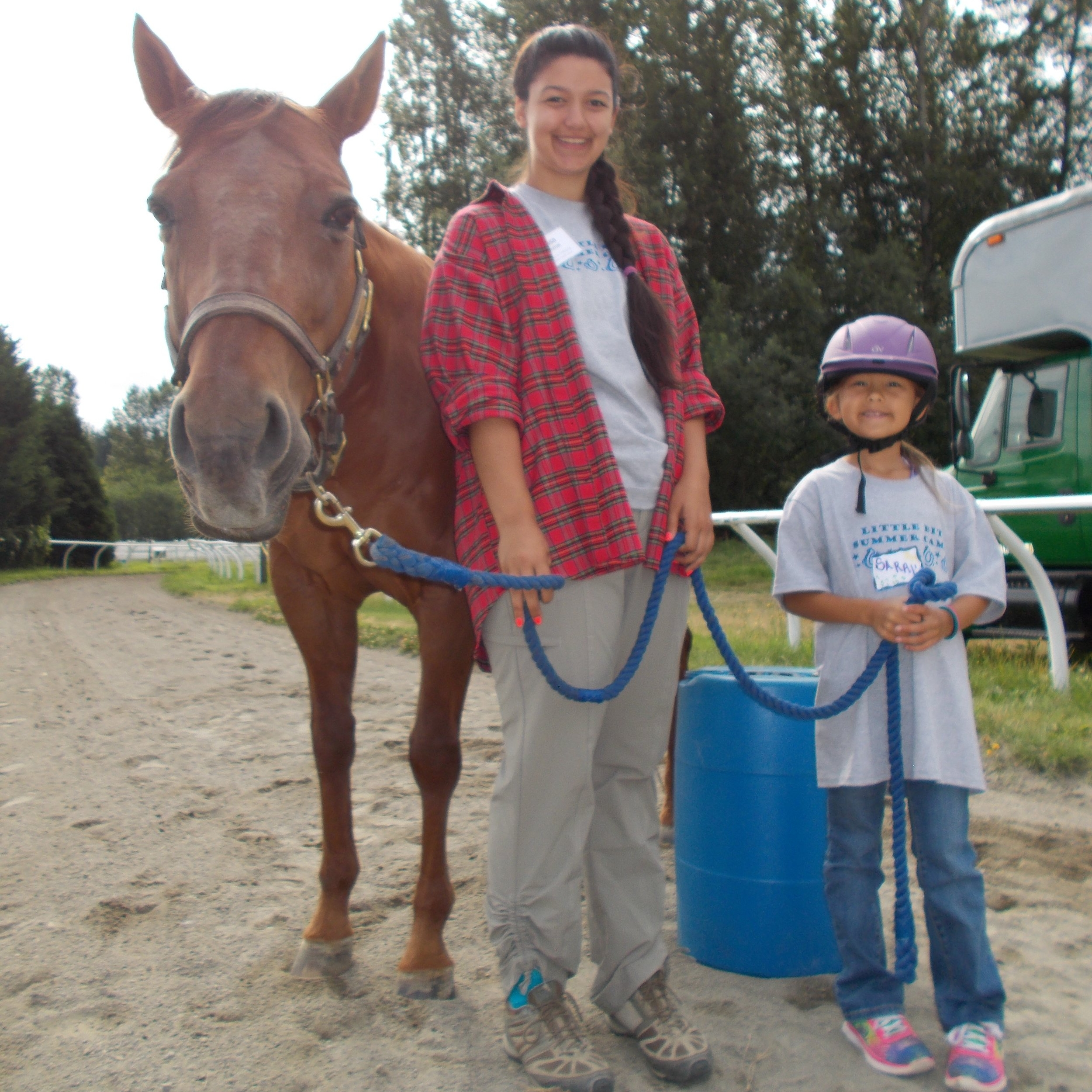 Two summer camp participants standing next to a horse and holding the reins together.