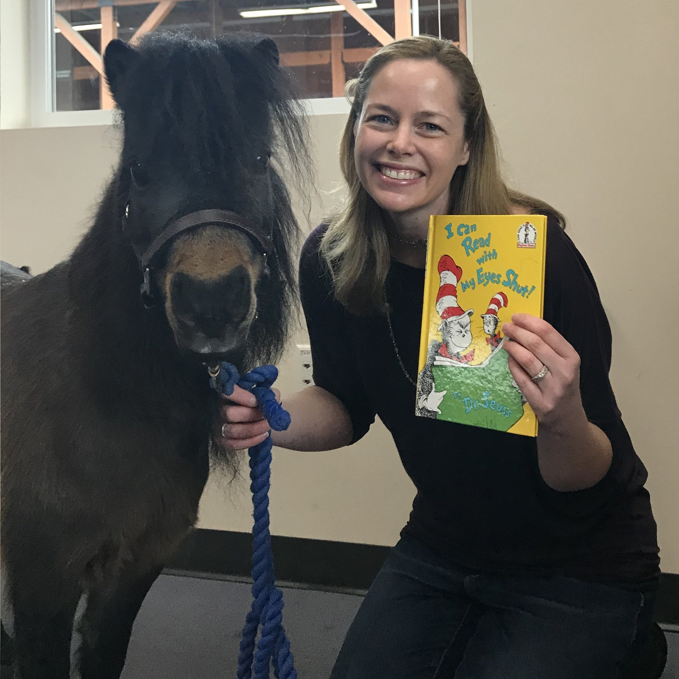 "Woman holding up the book ""I Can Read with My Eyes Shut,"" by Dr. Seuss. She is kneeling next to a brown mini horse."