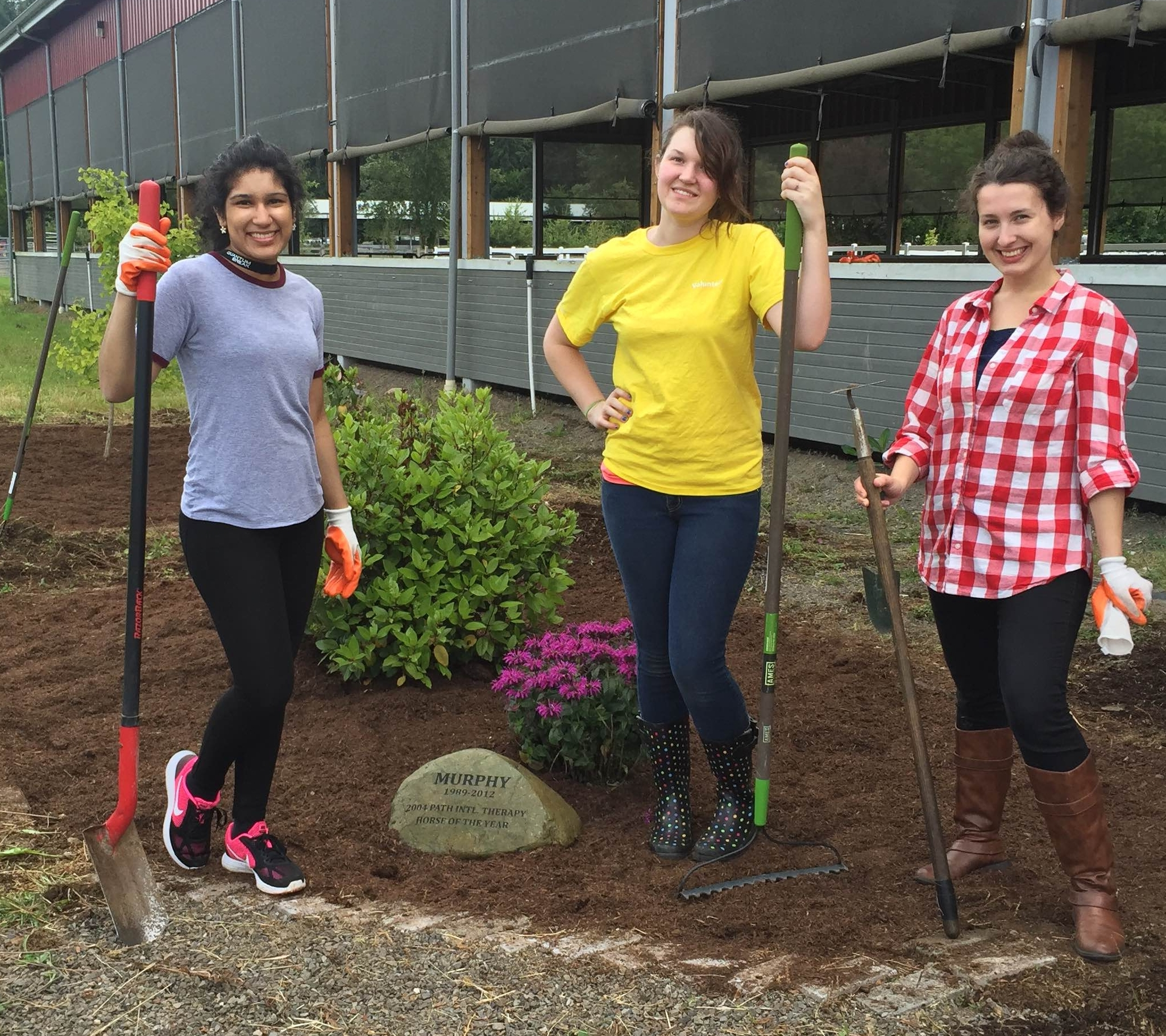 Three women holding shovels and rakes, standing in front of the Little Bit memorial garden.