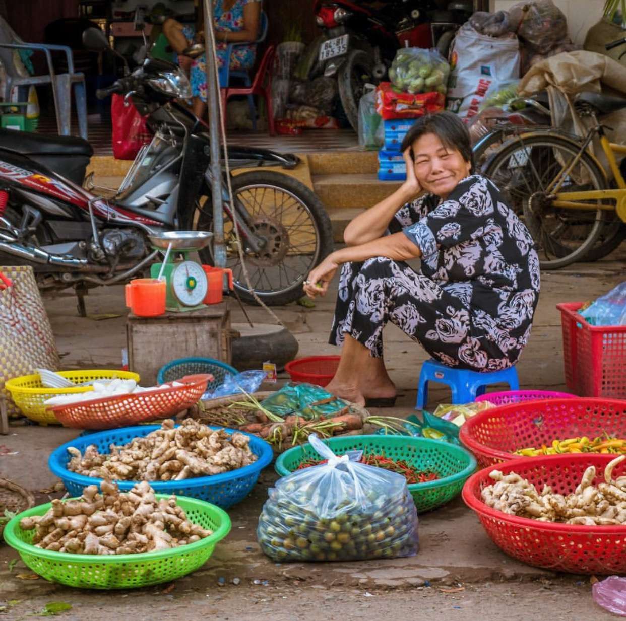 """""""After watching her neighboring vendors flag me down to photograph their grandchildren, their vegetables, their decapitated fish, and themselves, this woman gave me a gentle wave to snag my attention just as I was about to walk away,"""" Shannon says. """"More than any other city I visited in Vietnam, the people in Tra Vinh were delighted to have a foreigner at the market wielding a big smile, friendly curiosity, and a discreet camera.  Photo by Shannon O'Donnell ."""