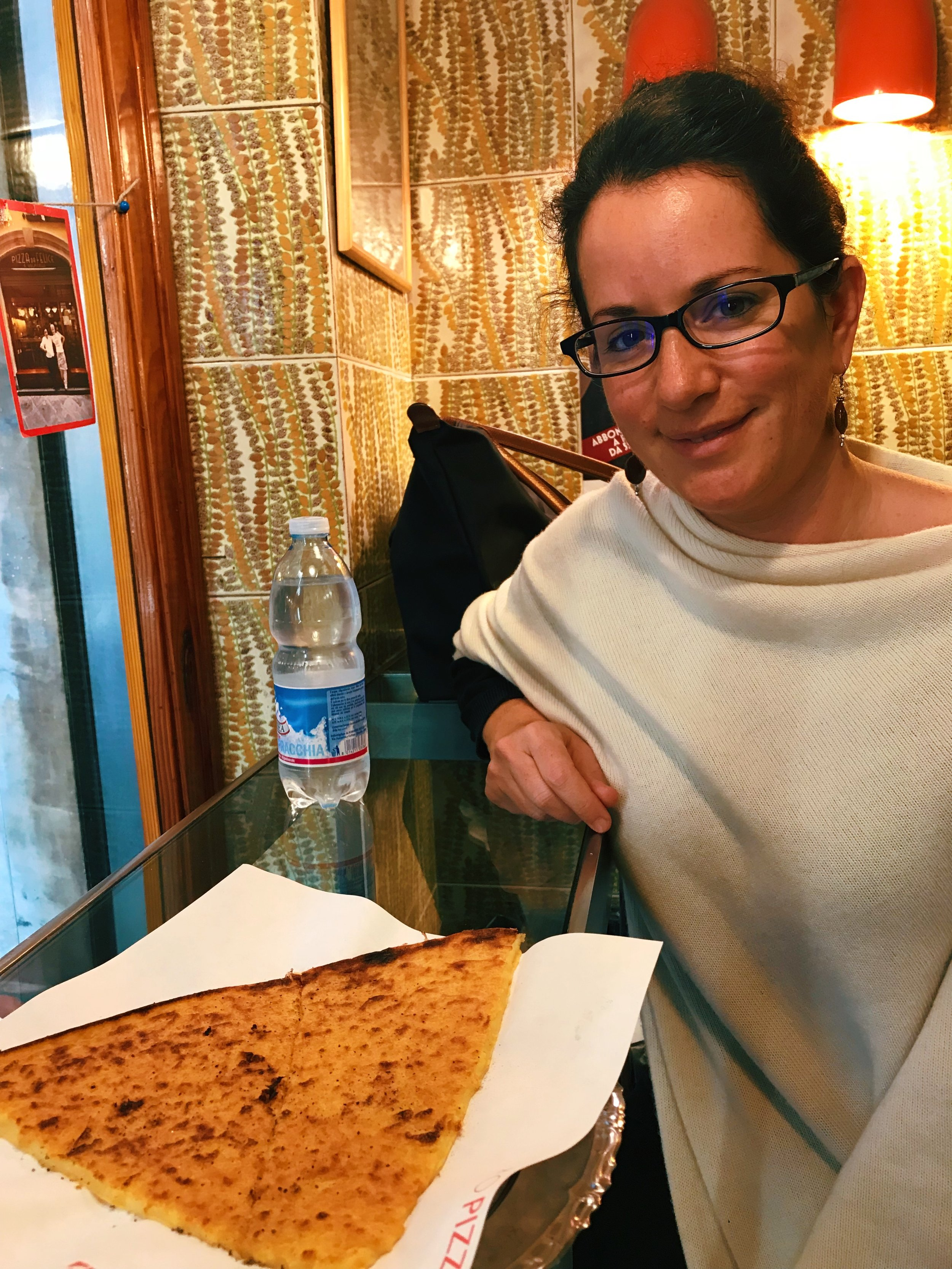 Toni about to dig into her cecina at  Pizzeria da Felice . These chickpea slices go by different names throughout Italy and they taste much more interesting than they look.