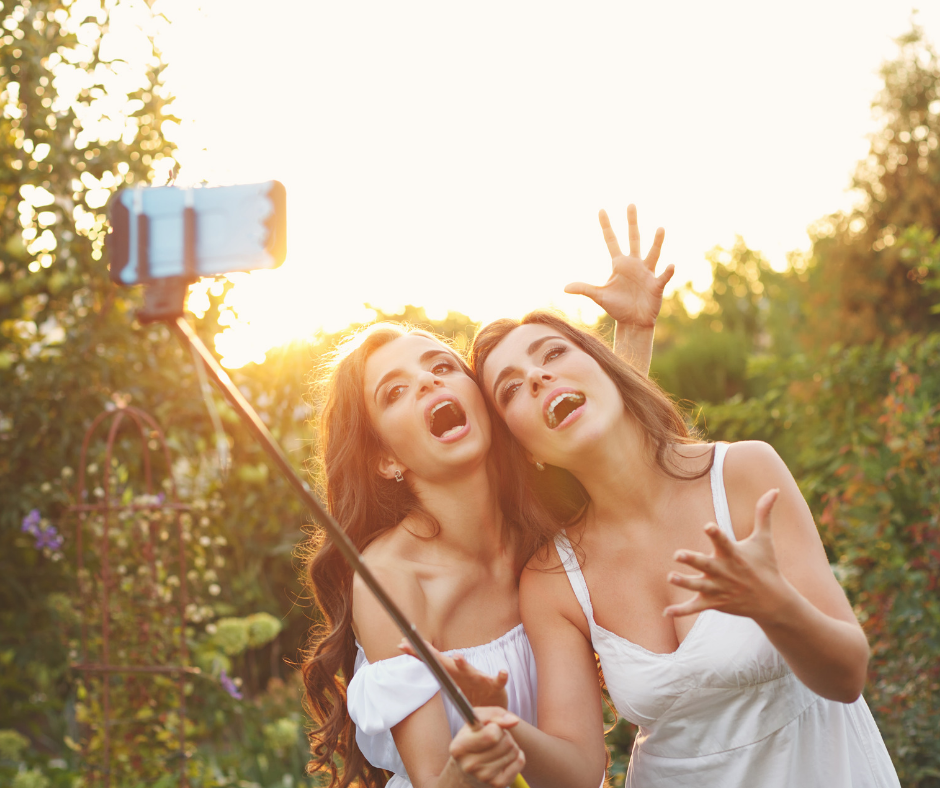 Women taking selfies in a forest with a selfie stick for Instagram