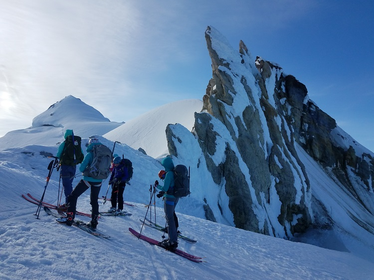 Teammates cluster and wait their turn to peek over the rim of the Sherman Crater on Mt. Baker.