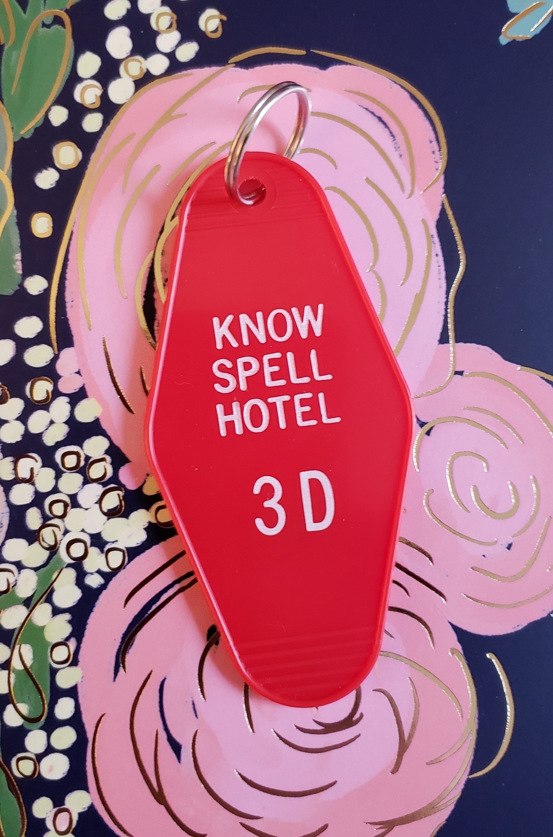 Know Spell Hotel Retro Keychain - Get checked in to the Know Spell Hotel with this retro hotel keychain! Miss Spell, Precious, and Ajax have you booked for room 3 D. Don't forget to return it to the front desk upon checkout... if you checkout... This 3 1/2