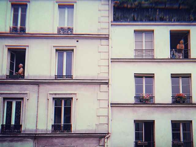Neighbors in Paris' 11th arrondissement lean out their windows to catch a glimpse of the military flyovers on Bastille Day, 2019. #latergram