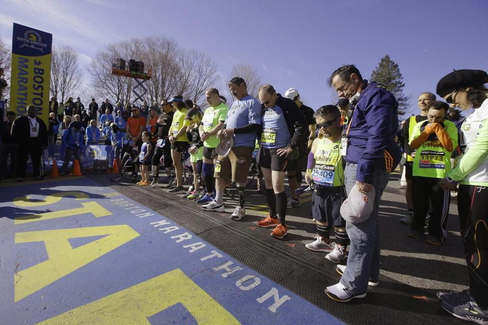 Boston Marathon race director Dave McGillivray (far right) paused at the start line during a moment of silence prior to the start for the mobility impaired participants.