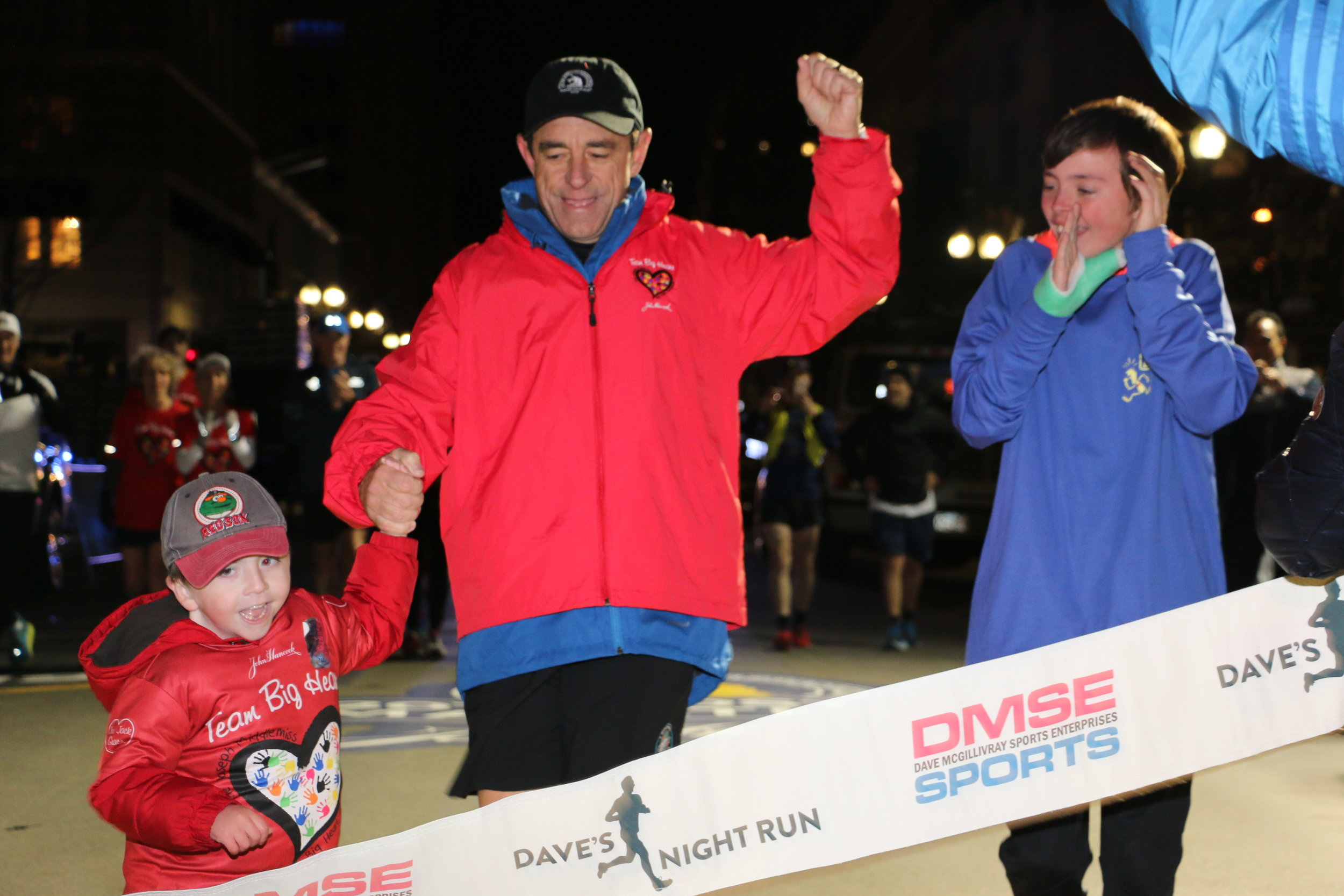Dave McGillivray crosses the finish line of the Boston Marathon holding hands with Jack Middlemiss, while McGillivray's son, Luke, cheers.   Bob McGillivray