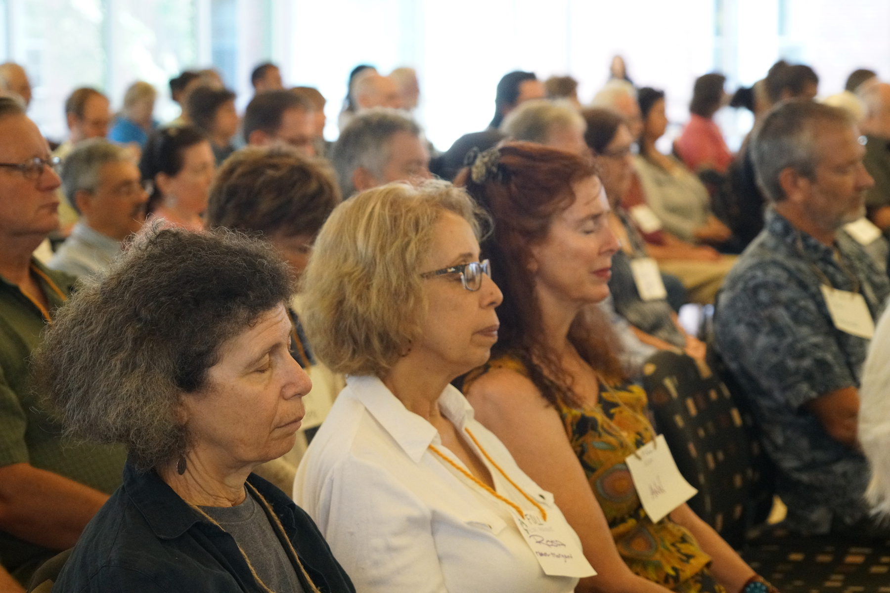 Participants close their eyes during a brief prayer led by Jul Bystrova during the conference's opening session. Photo by Teresa Konechne.