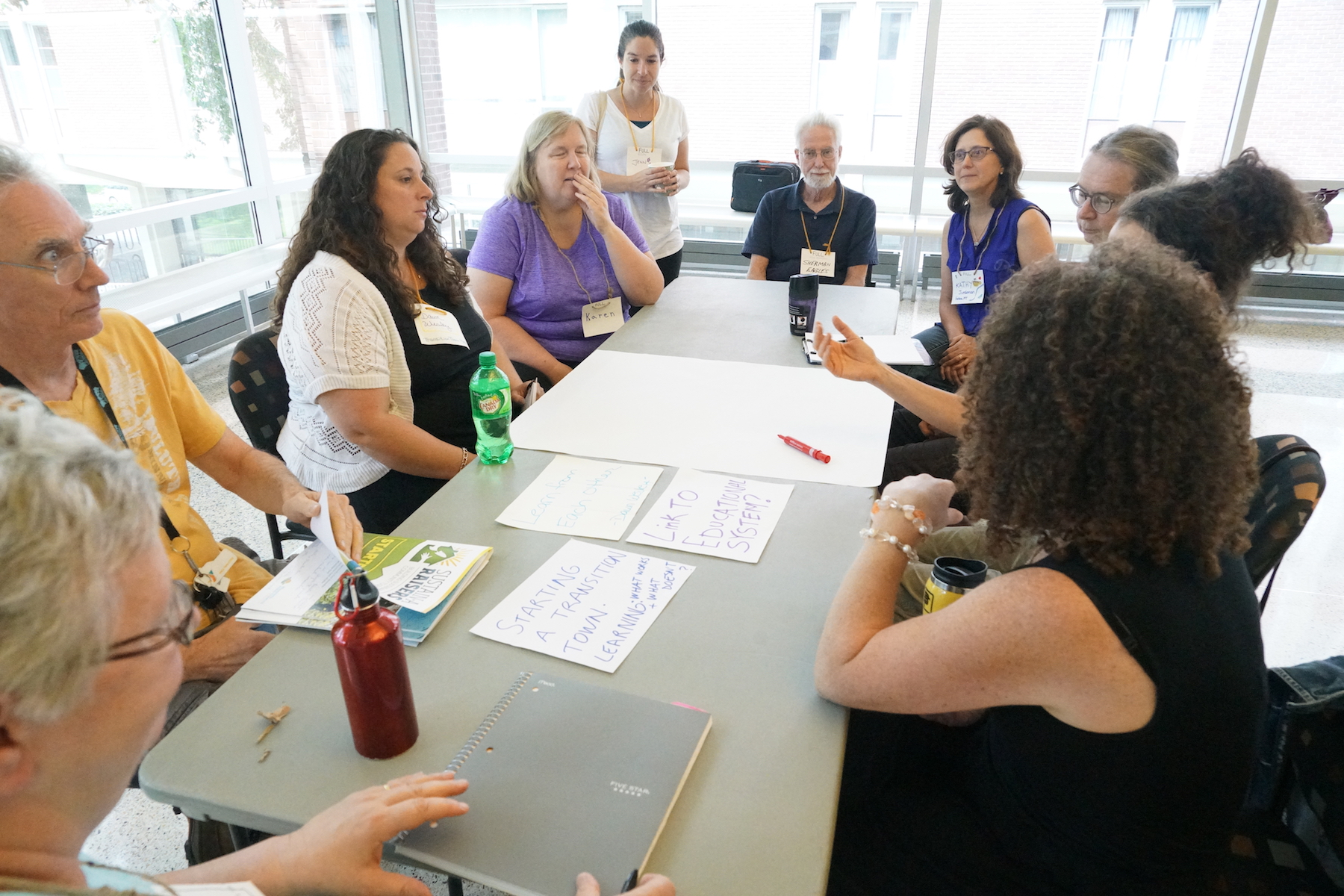 Sari Steuber, Sherman Eagles, Dawn Wesley, Kathy Juedeman, and others bring together three interrelated topics about education at their Open Space table. Photo by Teresa Konechne.