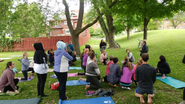 Emma Dines delivering a land acknowledgement to a thoughtful group before commencing their Yoga in the Park practice in downtown Kitchener.