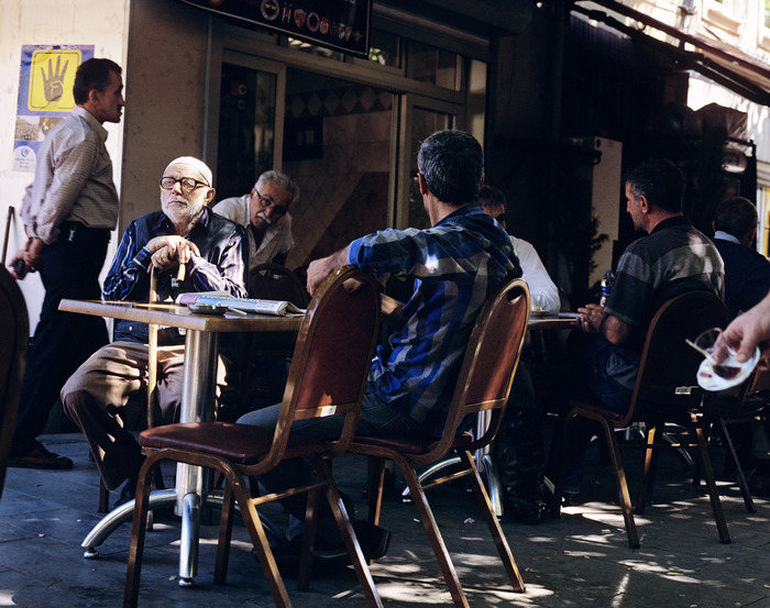 Men drinking tea in a cafe next to one of the many mosques in Istanbul. The yellow hand on the wall is the symbol for the Muslim Brotherhood.