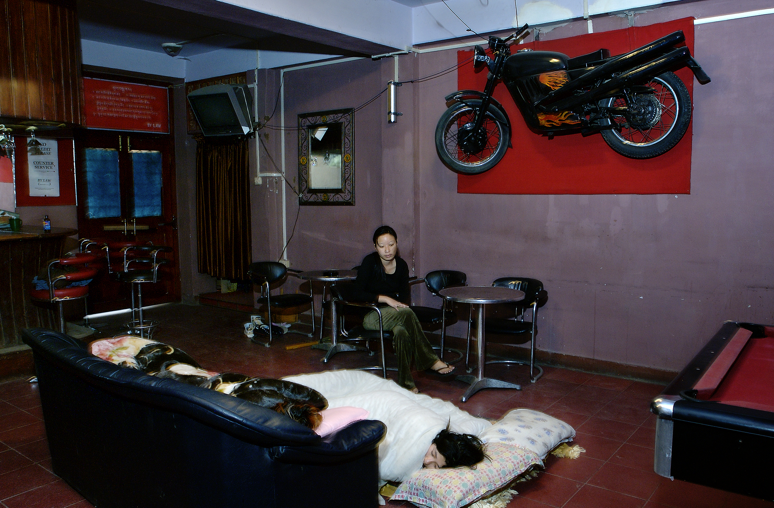 Tashi Lhamo    (sitting) and her friends sleep after business hours in The Twilight Lounge bar.   She is one of an increasing number of young people moving to the cities hoping to find work. 05.10.07 Thimphu  .