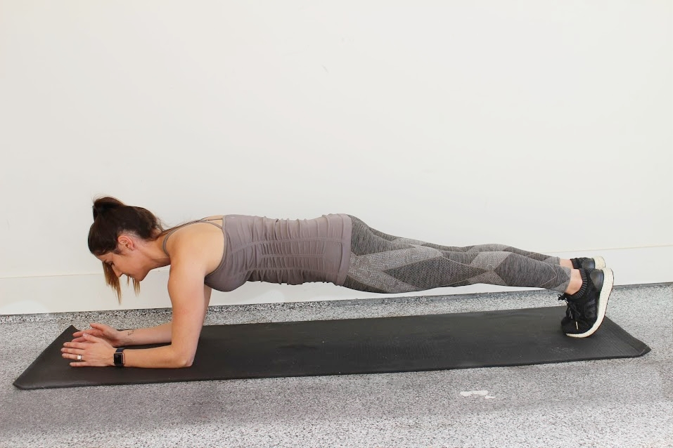 Forearm Plank - Place forearms on the floor with the elbows directly under the shoulders, arms parallel to the body about shoulder width apart.Extend legs behind you with your feet close together and hold.Make sure you are shifted forward on your toes, engaging core, glutes and quads.