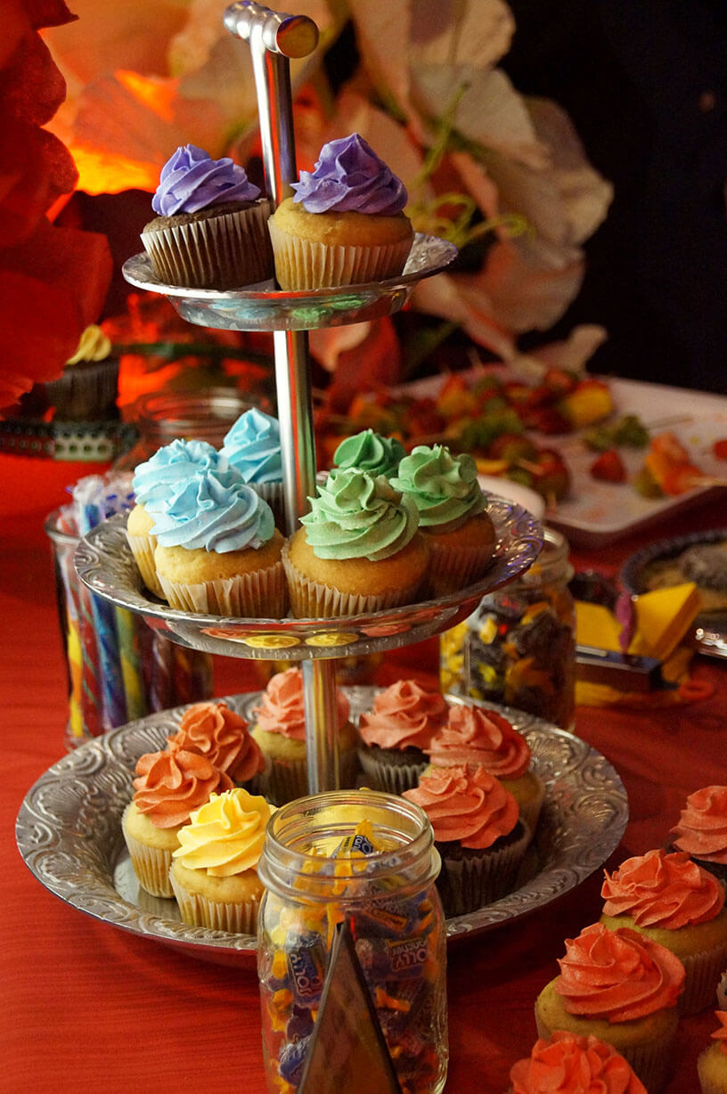 Rainbow cupcake display on 3-tiered silver platter on dessert/sweets table - Historia Wedding and Event Planning