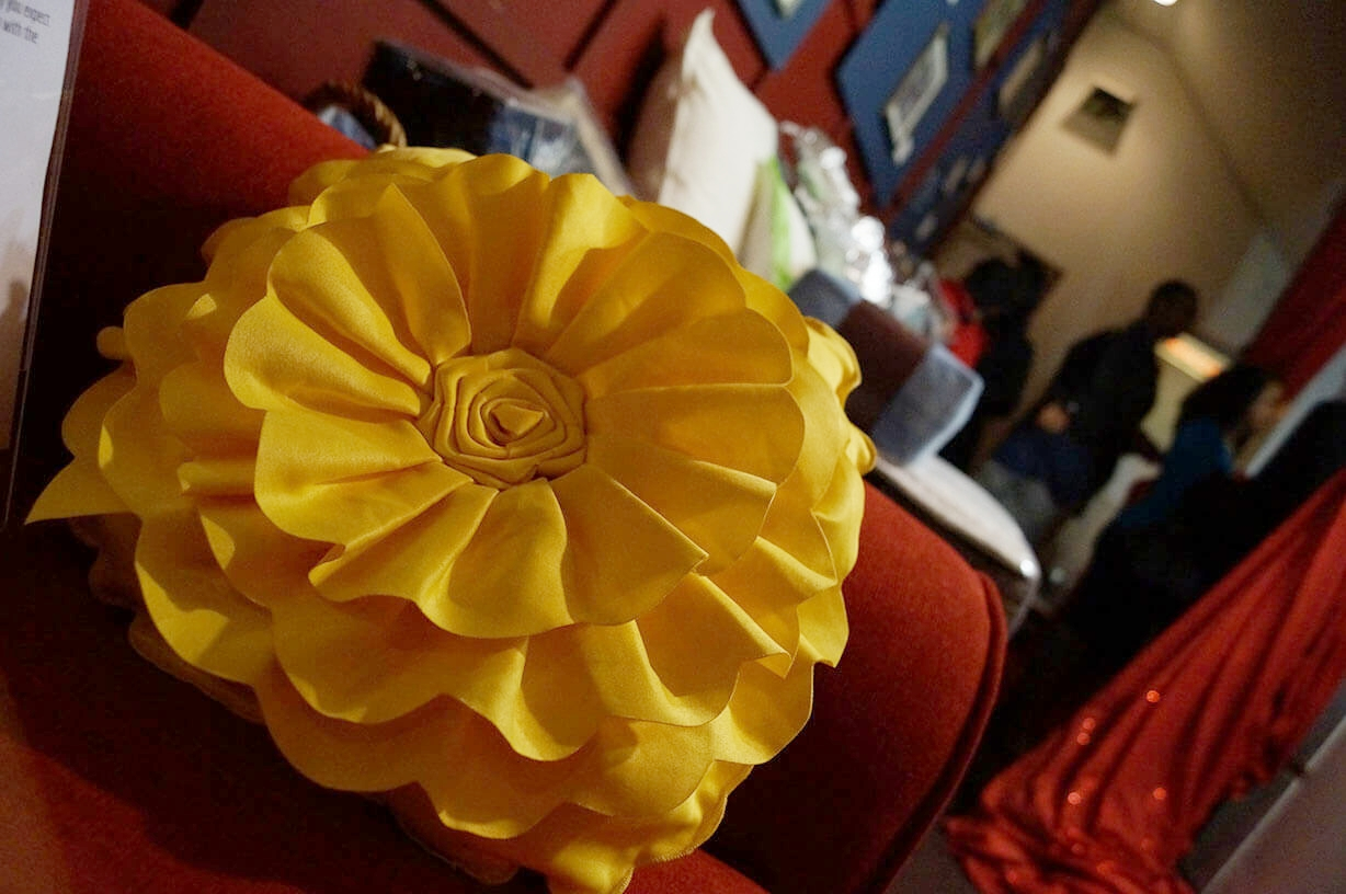 Yellow flower pillow on red sofa - Historia Wedding and Event Planning