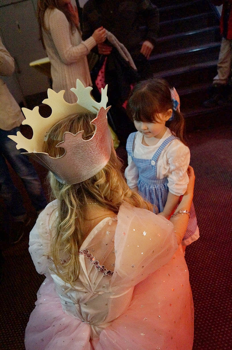 Glenda the Good Witch costumed event staff kneeling down with little girl dressed as Dorothy - Historia Wedding and Event Planning