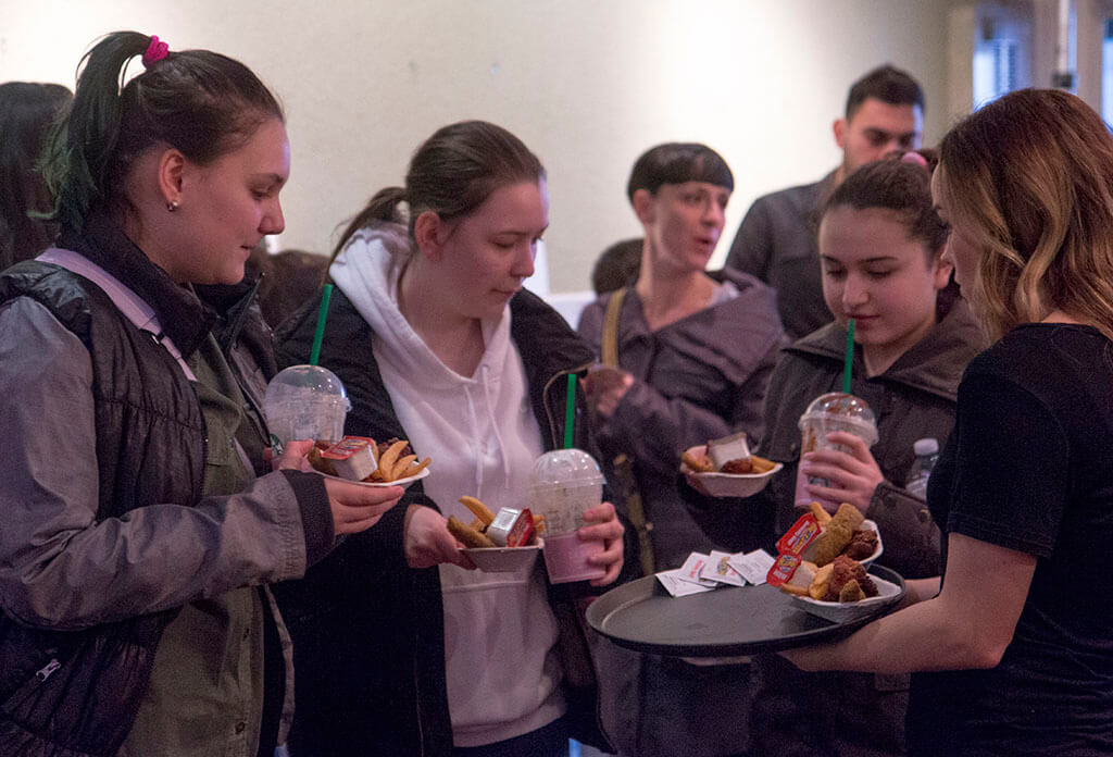 Event staff serving guests sponsored chicken wings and fries from St. Louis Bar and Grill - Historia Wedding and Event Planning
