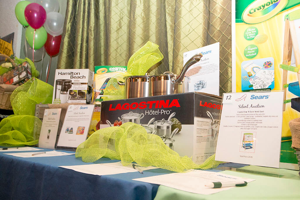 Table of sponsored event raffle/silent auction items with decorative green tulle - Historia Wedding and Event Planning