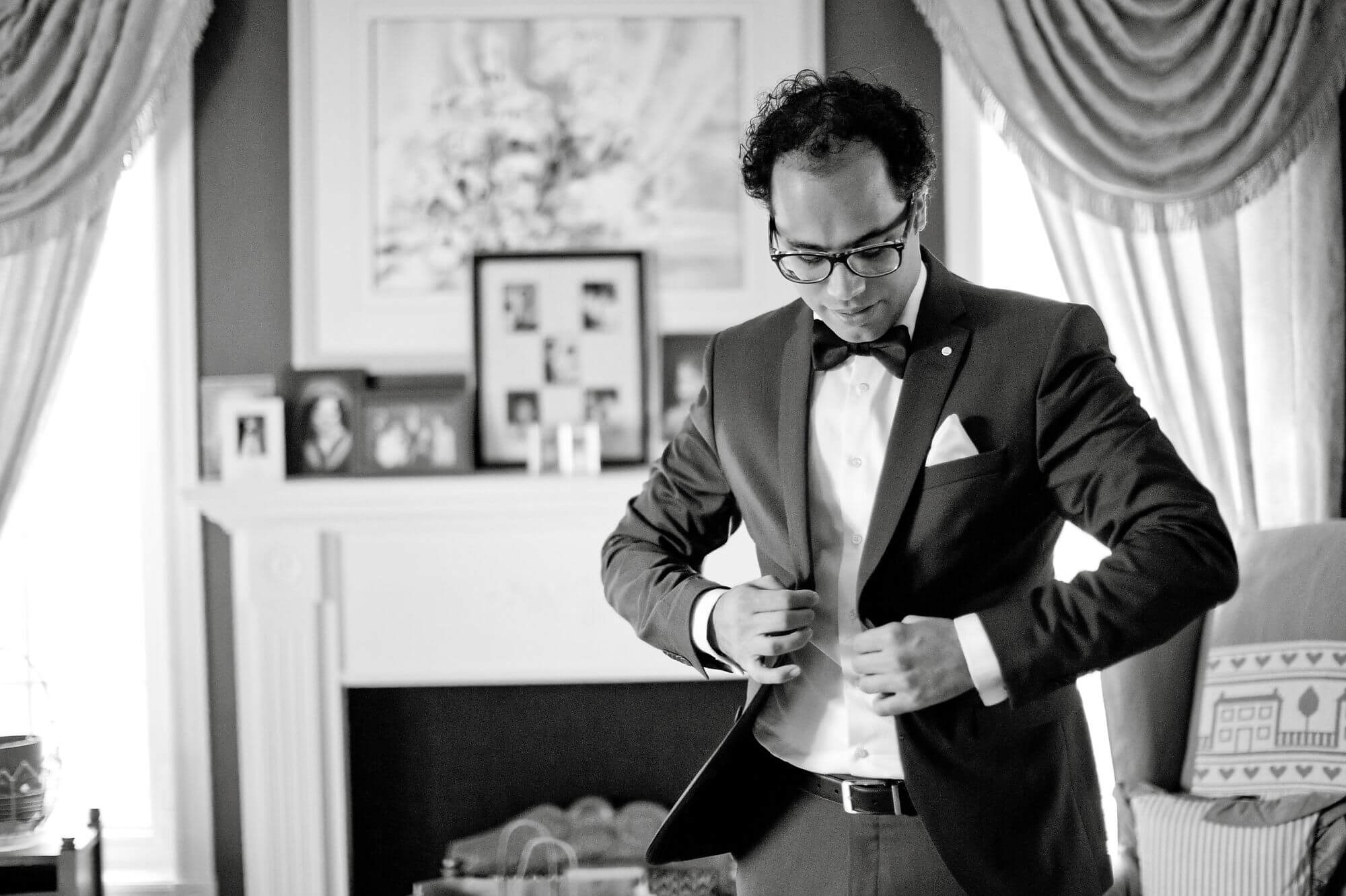 Black and white photo of groom getting ready, closing suit jacket - Niagara wedding - Historia Wedding and Event Planning