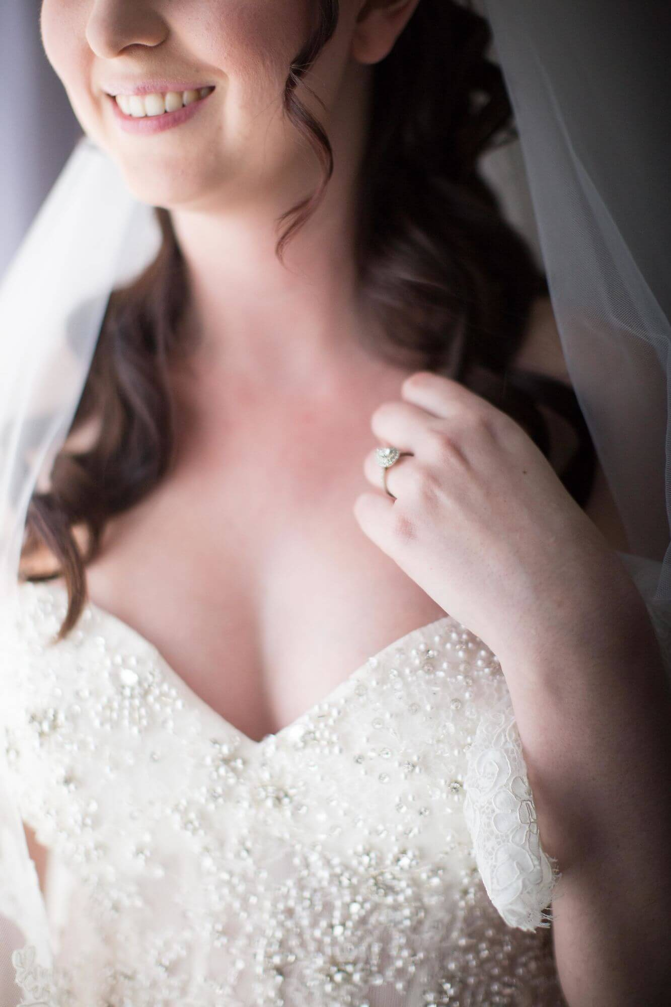 Photo of upper half of bride smiling to show bridal gown and engagement ring detail - Historia Wedding and Event Planning