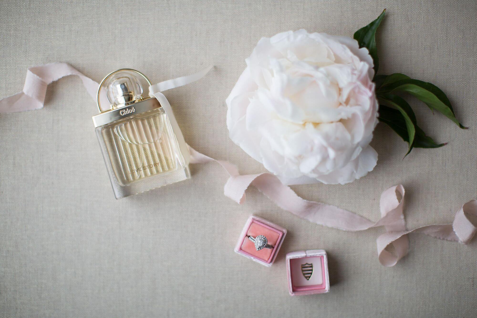 "Artistic photo of a white peony flower, Chloé ""Love Story"" perfume, pink ribbon and bride's engagement ring - Niagara wedding - Historia Wedding and Event Planning"