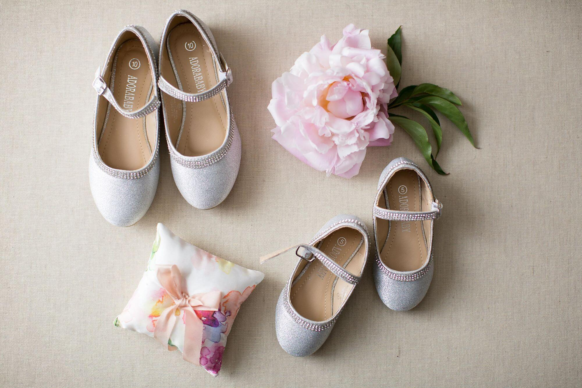 Artistic photo of flower girls' white dress shoes with floral watercolour ring pillow and pink peony flower - Historia Wedding and Event Planning