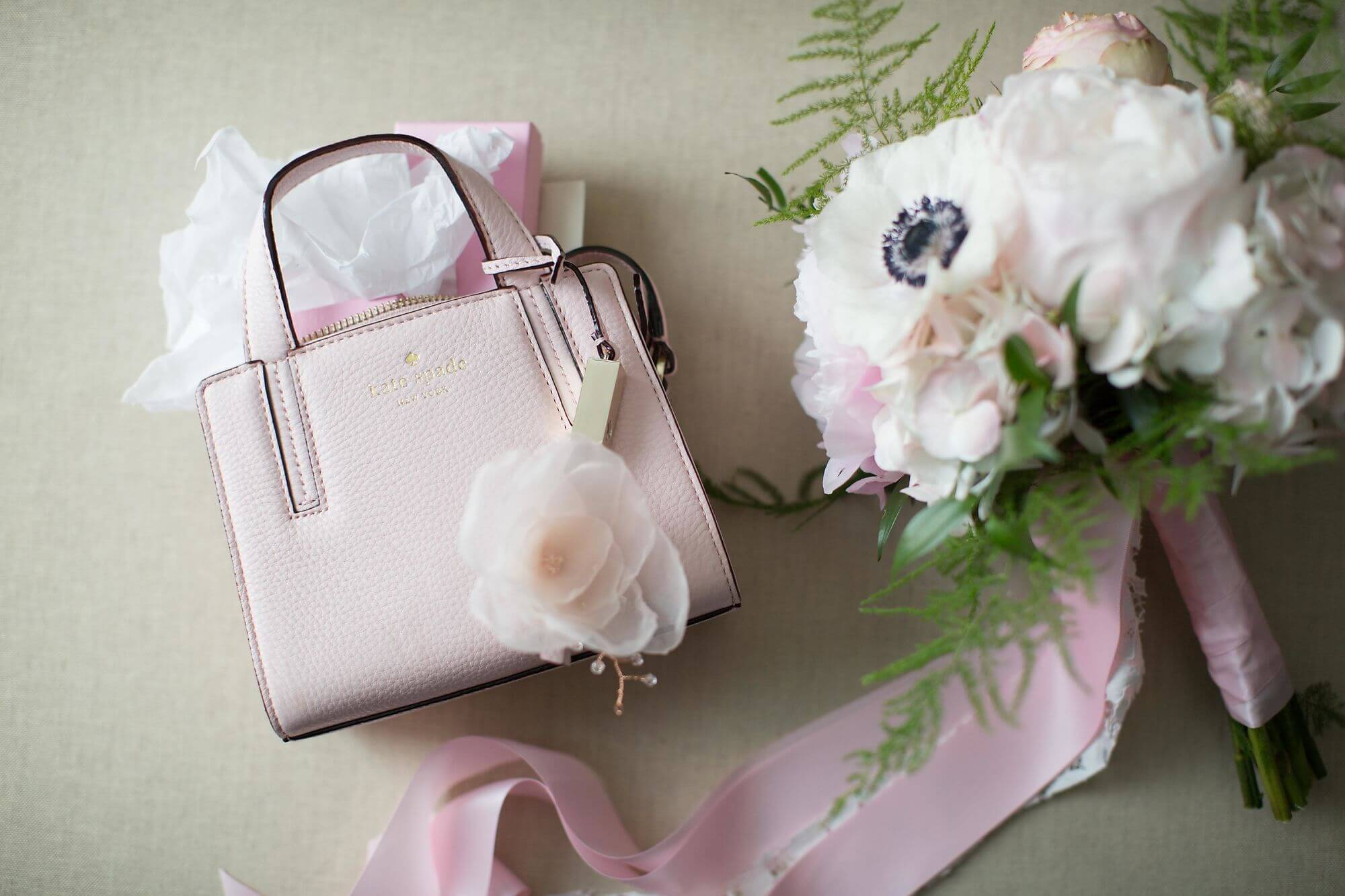 Artistic photo of petite white and blush pink bouquet with pink ribbon and baby pink Kate Spade clutch - Niagara wedding - Historia Wedding and Event Planning