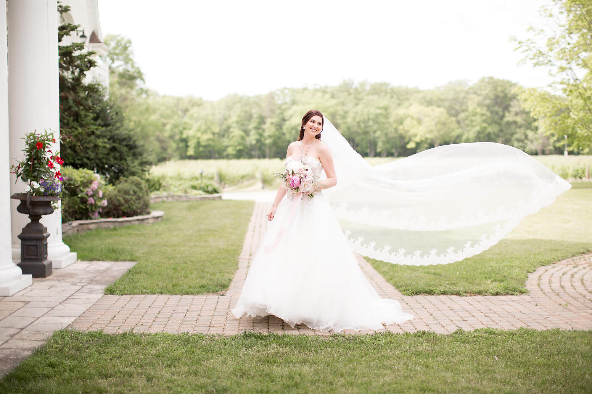 Whimsical photo of bride standing with veil blowing in the wind - Niagara wedding - Historia Wedding and Event Planning