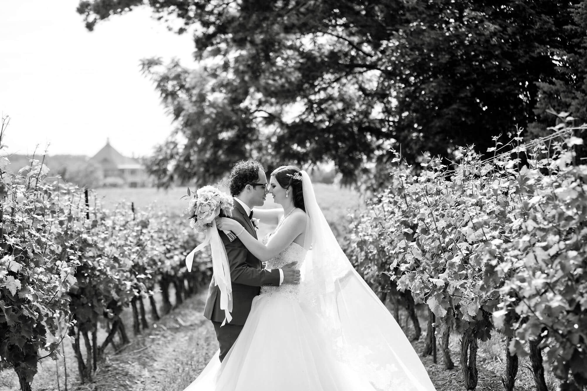 Black and white photo of bride and groom embracing in vineyard at Riverbend Inn and Vineyard - Niagara wedding - Historia Wedding and Event Planning