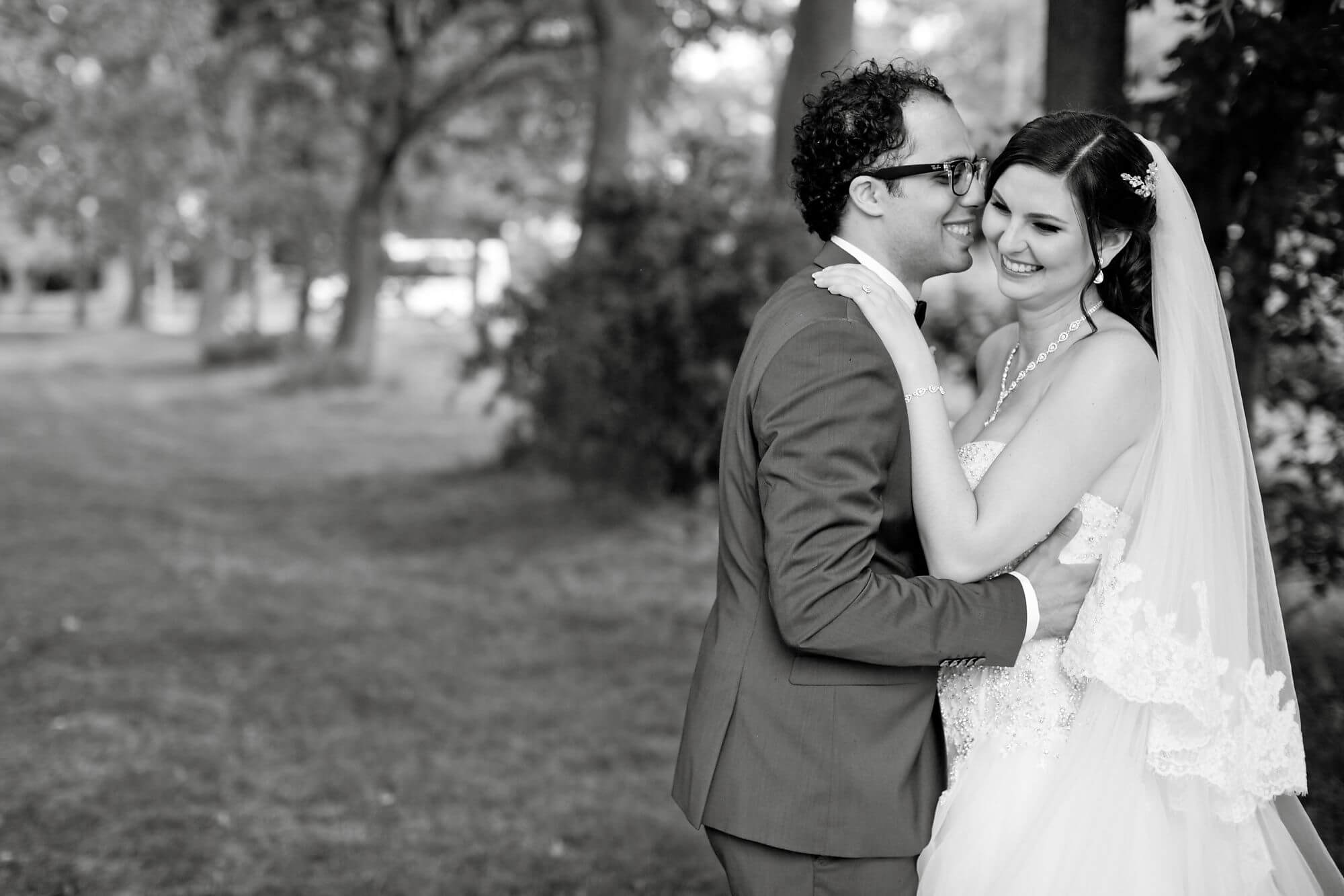 Black and white photo of bride and groom holding each other sweetly outside in nature - Niagara wedding - Historia Wedding and Event Planning