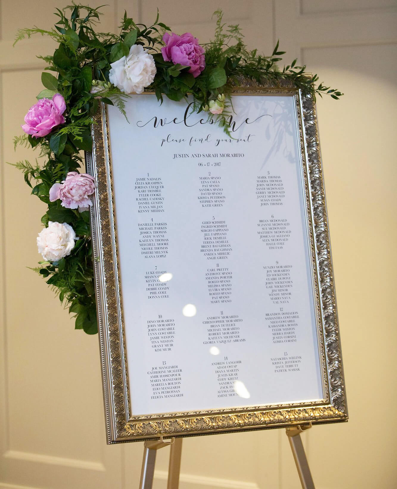 Elegant seating chart in gold frame on easel with white and pink peony leaf floral garland - Champagne, Blush and Gold Niagara Wedding - Historia Wedding and Event Planning