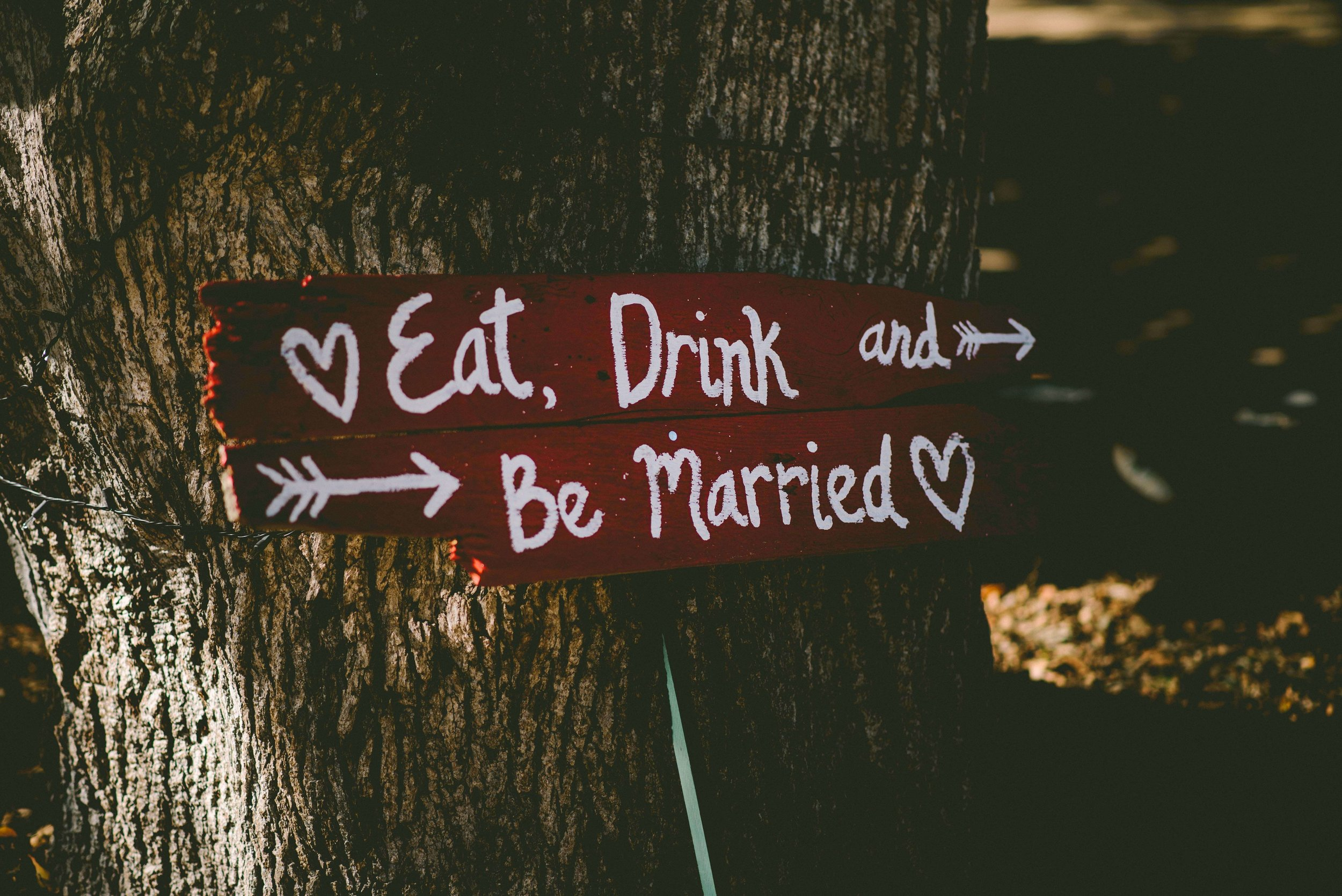 "Wedding signage leaning against a tree - ""Eat, Drink and Be Married"""